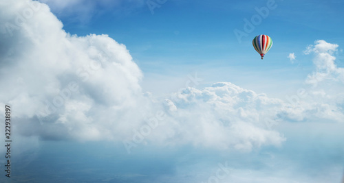 Colorful hot air balloon flying against blue cloudy sky.