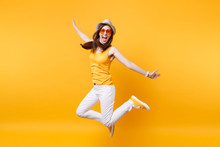 Portrait Of Excited Smiling Young Jumping High Woman In Straw Summer Hat, Orange Glasses Copy Space Isolated On Yellow Background. People Sincere Emotions, Passion Lifestyle Concept. Advertising Area.