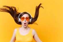 Portrait Of Excited Cheerful Laughter Funny Comic Woman In Orange Glasses In Headphones With Fluttering Hair Isolated On Yellow Background. People Sincere Emotions, Lifestyle Concept. Advertising Area