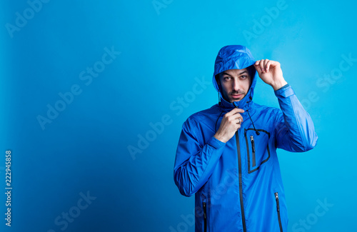 Photo Portrait of a young man in a studio with anorak on a blue background