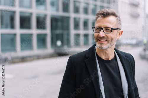 Photographie  Mature smiling man with glasses wearing black coat