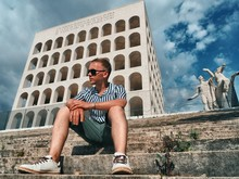 A Blond Man In A Striped Shirt Sitting On The Steps Of The Square Colosseum In Rome, Non-standard Attractions