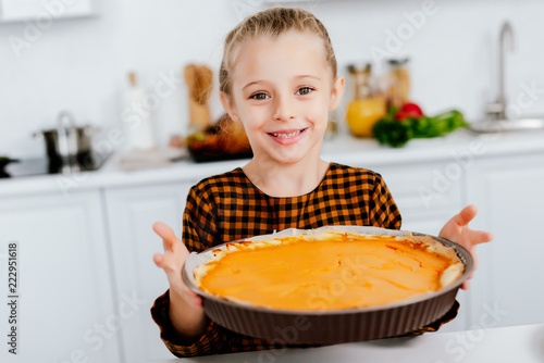 happy little child holding baking tray with thanksgiving pie Wallpaper Mural