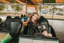 Excited Woman Riding Bumper Car