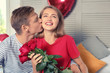 Happy young couple with red roses sitting on bed at home