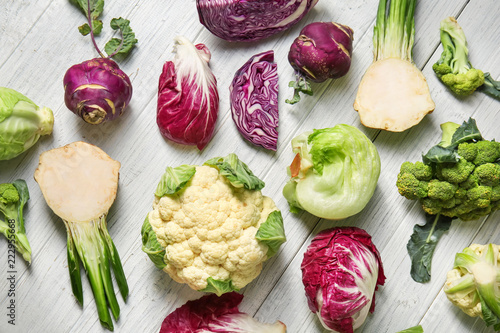 Different types of cabbage on light wooden background Wallpaper Mural