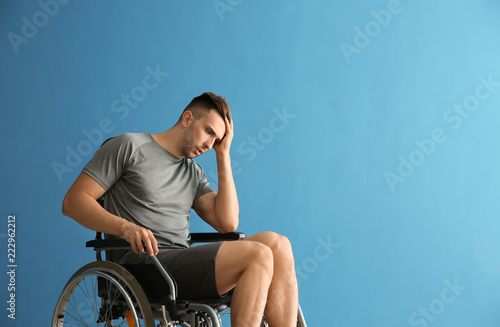Depressed young man sitting in wheelchair against color background