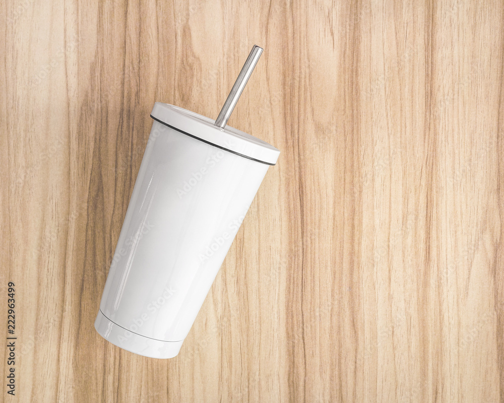 Fototapeta White steel mug with tube on wood background. Insulated container for keep your drink.