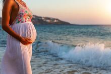 Schwangere Frau In Weißem Sommerkleid Steht Zum Sonnenuntergang Am Meer