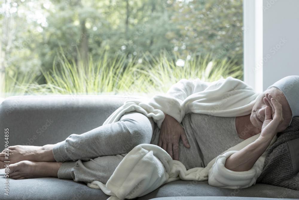 Fototapeta Sick woman with a headache lying on a sofa
