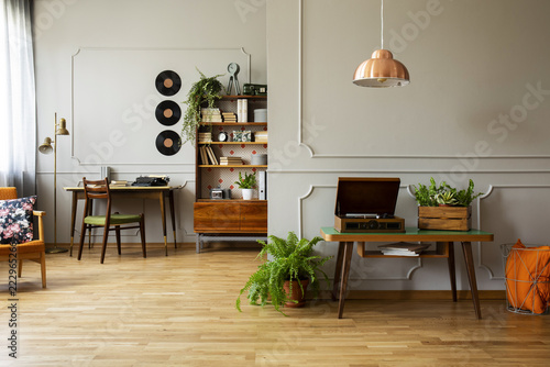 Foto Record player and plant on wooden table in grey apartment interior with lamp and vinyl
