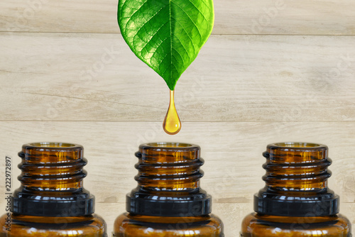 Fotografie, Obraz  Pure and organic essential oil dripping from a green plant into a dark amber bot