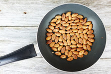 Roasted Almonds In Dark Pan Against Rustic Wooden Background