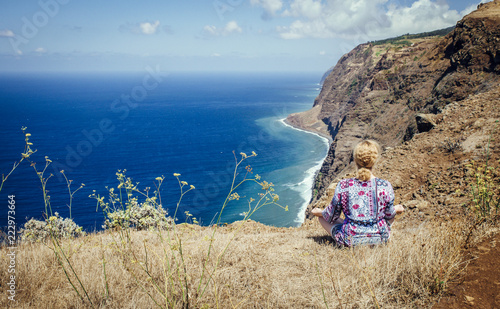 Woman in floral summer clothes sit on the cliff in mediation