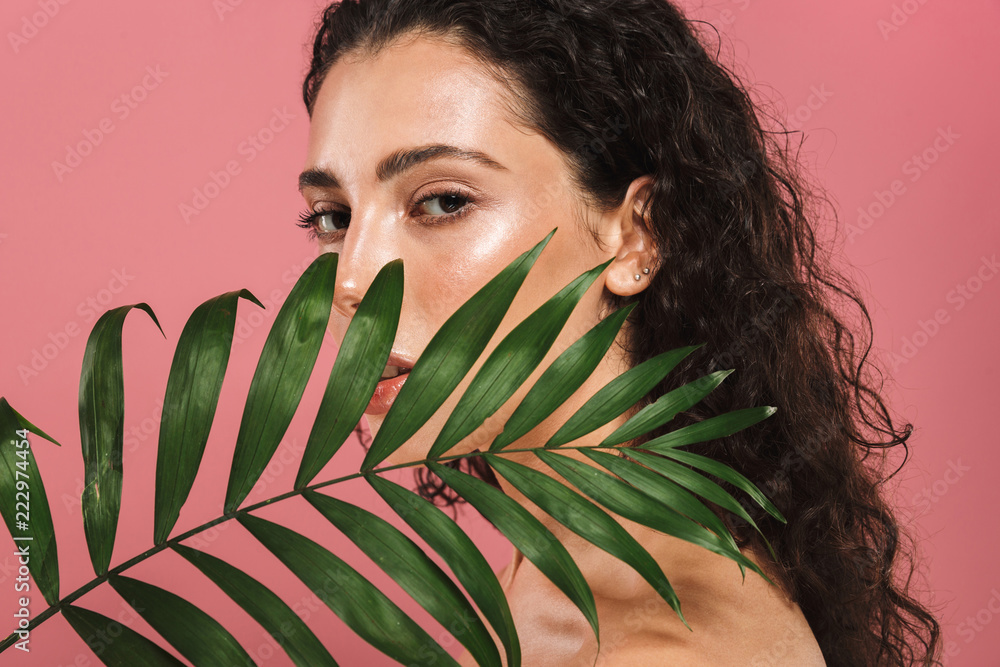 Fototapeta Portrait of half naked beautiful woman with long hair holding green leaf, isolated over pink background