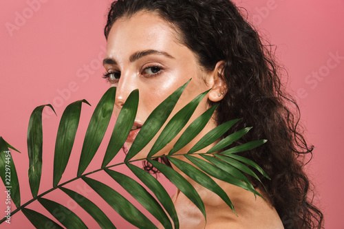 Obraz Portrait of half naked beautiful woman with long hair holding green leaf, isolated over pink background - fototapety do salonu