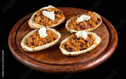 Tuinposter Buffet, Bar Potato topped with Chilli con carne and sour cream isolated on black background