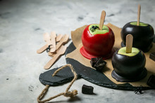 Halloween Style Sweets - Black Poisoned, Red And Orange Caramel Apples, Rustic Background