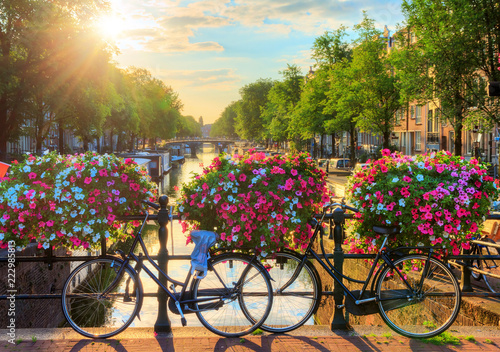 Photo sur Toile Europe Centrale Beautiful summer sunrise on the famous UNESCO world heritage canals of Amsterdam, The Netherlands, with vibrant flowers and bicycles on a bridge
