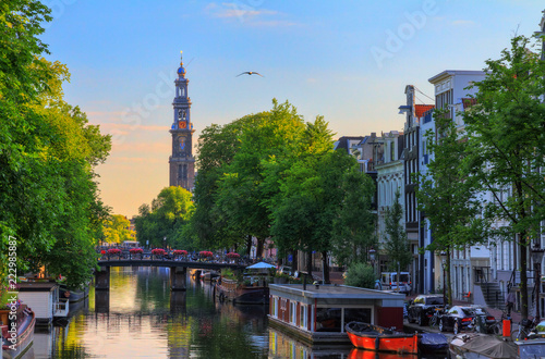 UNESCO world heritage Prinsengracht canal with the Westerkerk (Western church) on a summer morning with a blue sky in Amsterdam, The Netherlands