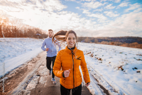 Poster Glisse hiver Fitness couple winter morning exercise at snowy mountain.