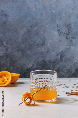 Glass of Scotch Whiskey orange juice alcohol cocktail with swirled orange peel on skewer and cinnamon sticks standing on white marble table with golden holiday Christmas stars confetti.