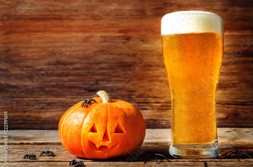 Poster Bier / Cider Glass of cold light beer with pumpkin on a wood background for Halloween