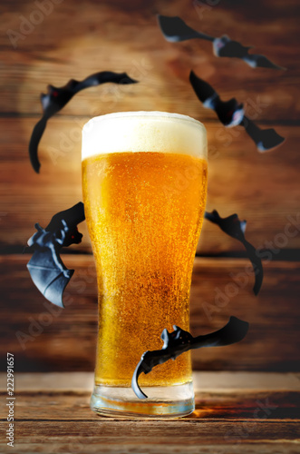 Poster Bier / Cider Glass of cold light beer with flying bats on a wood background for Halloween