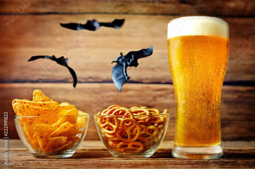 Poster Bier / Cider Glass of cold light beer with snacks on a wood background for Halloween
