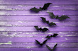 canvas print picture - halloween, decoration and scary concept - black bats flying over ultra violet shabby boards background