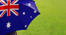 Australian Flag Umbrella. Close Up Of Printed Umbrella Over Green Field Lawn Background. Weather Forecast Concept.