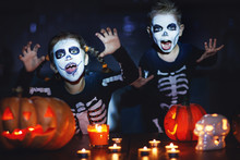 Happy Halloween! Children In Costume Of Skeletons With Pumpkins And Candles In Dark.