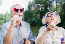 Soap Bubbles. Funny Active Couple Of Pensioners Standing On The Bridge And Blowing Soap Bubbles