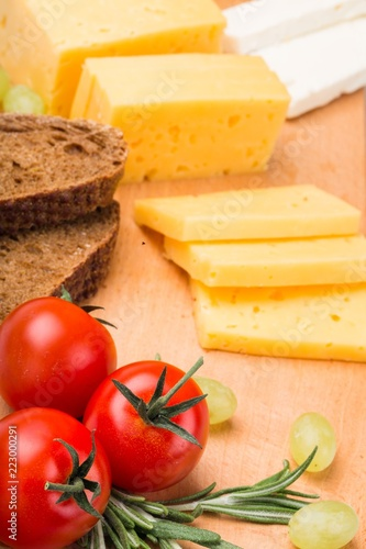 Cheese, Tomatoes and Bread on the Wooden Platter - Close Up