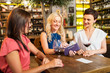leisure, payment and lifestyle concept - happy women with money in wallet paying bill at restaurant or wine bar