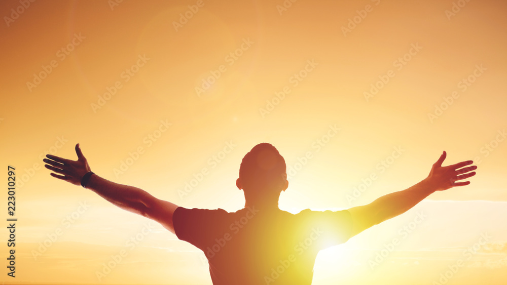 Fototapeta Young man standing outstretched at sunset. Bright solar glow and sky