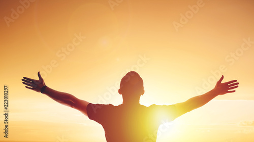 Fotografiet Young man standing outstretched at sunset