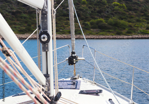 The mainmast is a mast and a twirled staysail on a sailing yacht and bow rails against the backdrop of a picturesque green bay with a yacht anchored Tablou Canvas