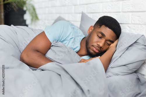 Young african-american man sleeping in bed at home Wallpaper Mural