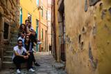 Fototapeta Uliczki - Company of young people sitting on a narrow street of Porto, Portugal.