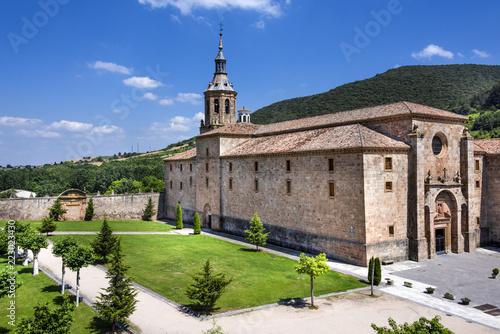 Fototapeta Spain, La Rioja, San Millan de la Cogolla: Panoramic view of famous Monastery of San Millan de Yuso with public park, hills and blue sky