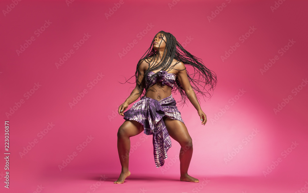 Fototapety, obrazy: Beautiful African Black girl wearing traditional colorful African outfit does a dramatic dance move against a colorful pink background