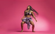 canvas print picture - Beautiful African Black girl wearing traditional colorful African outfit does a dramatic dance move against a colorful pink background
