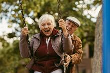 Senior Man Pushing His Partner On Swing