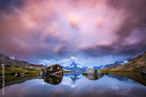Beautiful sunrise with pink clouds at lake Stellisee with a view of the Matterhorn #223035657