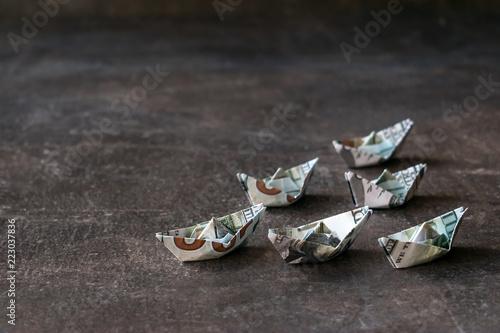 Fotografía  Origami ships from US dollars on a dark background