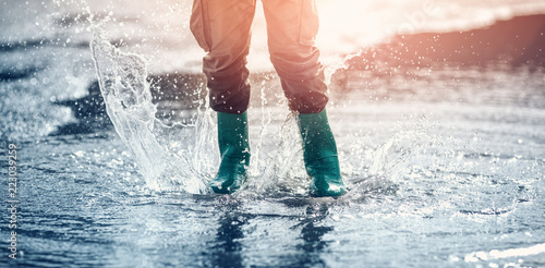Child walking in wellies in puddle on rainy weather Fototapeta
