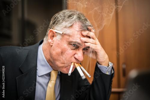Fotografía  Nervous businessman smoking many cigarettes at once