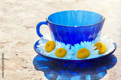 Drink beverage from chamomile herbs in tea blue glass cup