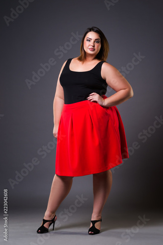 Plus size fashion model in red skirt, fat woman on gray background, overweight f Fototapet